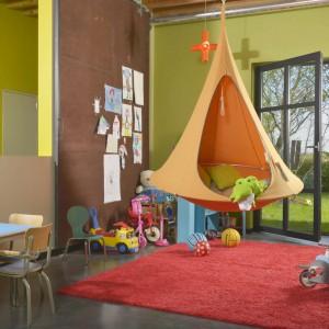 Hamak-huśtawka w kształcie namiotu, zawieszony w centrum dziecięcego pokoju zainspiruje maluchy do zabawy, jak również sprawi, że wnętrze zyska ciekawy wygląd. Należy jednak pamiętać, by ze względów bezpieczeństwa zawiesić go na niewielkiej wysokości, najlepiej nad dywanem. Fot. KLS Living.