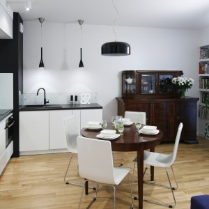 Z bielą mebli kuchennych harmonizują z białymi krzesłami przy stylizowanym, drewnianym stole. Projekt: Ewelina Para. Fot. Bartosz Jarosz.