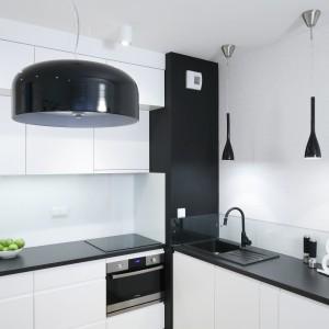 Czarne blaty z laminatu imitującego granit zapewniają sporą powierzchnię roboczą. To właśnie na nich pani domu przygotowuje potrawy dla siebie lub swoich gości. Projekt: Ewelina Para. Fot. Bartosz Jarosz.