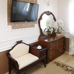 W sypialni znalazło się miejsce na elegancką komodę z lustrem. Ciemne meble kontrastują z jasną ścianą. Na przeciwko łóżka powtórzono dekoracyjny motyw: połączenie sztukaterii i wzorzystej tapety. Fot. Bartosz Jarosz.