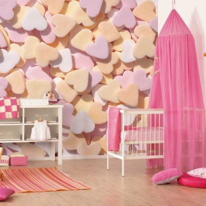 Fototapeta w serduszka oraz różowy baldachim nad łóżeczkiem sprawią, że wnętrze zyska słodki dziewczęcy charakter. Fot. IDecor.
