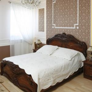 W sypialni połączono eleganckie beże i brązy z klasycznymi, bogato zdobionymi formami mebli. Sztukateria, starannie dobrane oświetlenie tworzą spójne, ponadczasowe wnętrze.  Fot. Bartosz Jarosz.
