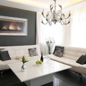 Elegancki salon urządzono w czerni i bieli. Białe sofy na lekki nóżkach uzupełnia stolik z lakierowanym na wysoki połysk obszernym blatem. Projekt: Łukasz Sałek. Fot. Bartosz Jarosz.