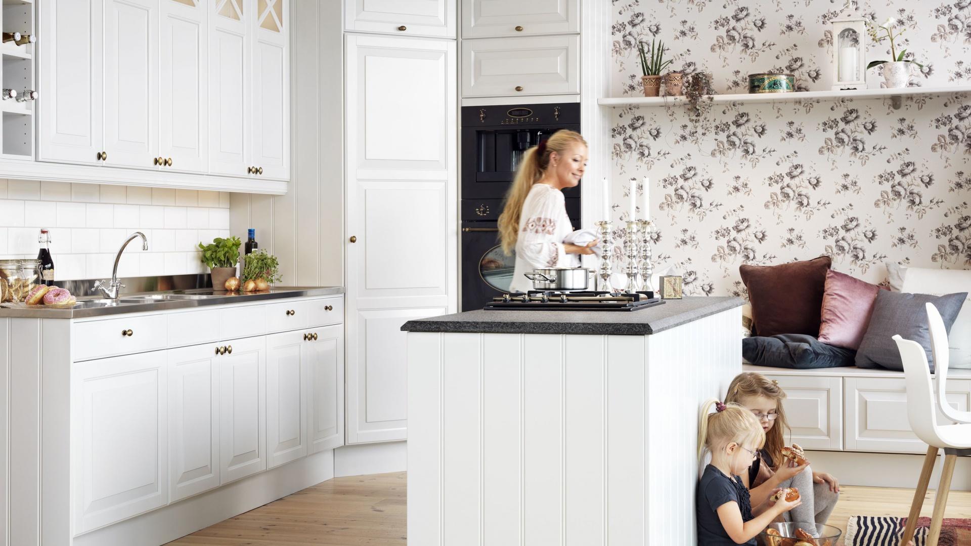 Kuchnia z wyspą sprzyja interakcji domowników. W tej klasycznej, przytulnej kuchni wyspa jest zdobiona pionowymi frezowaniami, wpisując się idealnie w rodzinną atmosferę pomieszczenia. Fot. Ballingslov.