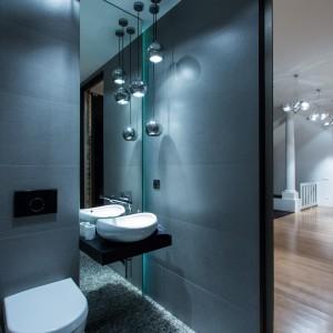 W mieszkaniu są trzy łazienki, jedną z nich wykończono ciemnoszarymi płytkami, które pięknie harmonizują z dekoracyjnym oświetleniem nad umywalką. Duże lustro za umywalką optycznie powiększa przestrzeń niewielkiego pomieszczenia. Fot. Marek Białokoz.
