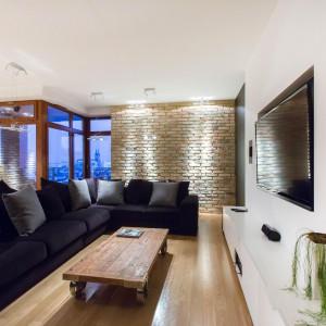 W obszernym salonie, przytulność buduje naturalna cegła na ścianie, drewniana podłoga oraz duży narożnik z ogromną ilością dekoracyjnych poduszek. Fot. Marek Białokoz.