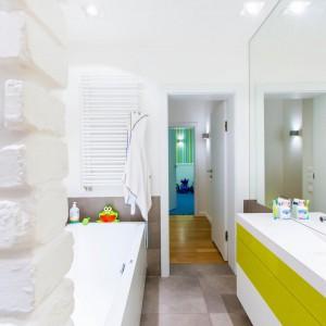 Łazienka położona na przeciwko pokoju dziecięcego, została wykończona w jasnych, wesołych kolorach. Cegłę pomalowano na biało, a szafkę umywalkową ożywiono intensywną, energetyzującą żółcią. Fot. Marek Białokoz.