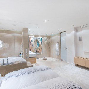 Dużą sypialnię połączono z luksusowym salonem kąpielowym. Funkcje spajają transparentne przeszklenia oraz jednorodna posadzka na podłodze. Fot. Marek Białokoz.