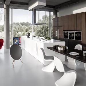 Biała wyspa kuchenna i kultowe już białe krzesła harmonizują z jasnoszarą podłogą. Taką chłodną, sterylną aranżację ociepla wysoka zabudowa kuchenna w kolorze ciepłego, czekoladowego drewna. Fot. Zajc Kuchnie.