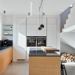 Szara podłoga, białe ściany i wysoka zabudowa kuchenna stanowią eleganckie, chłodne tło dla mebli w ciepłym kolorze drewna, zwieńczonych ciemnoszarym blatem. Fot. Atlas Meble Kuchenne.