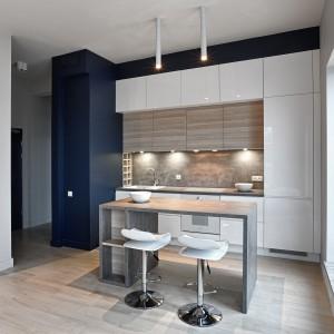 Biała zabudowa wykończona na wysoki połysk jest orzeźwiającym akcentem w kuchni, ocieplonej zgaszonymi kolorami drewna na blacie wyspy kuchennej i na frontach głębszego rzędu szafek górnych. Fot. Atlas Meble Kuchenne, kuchnia Patrycja.