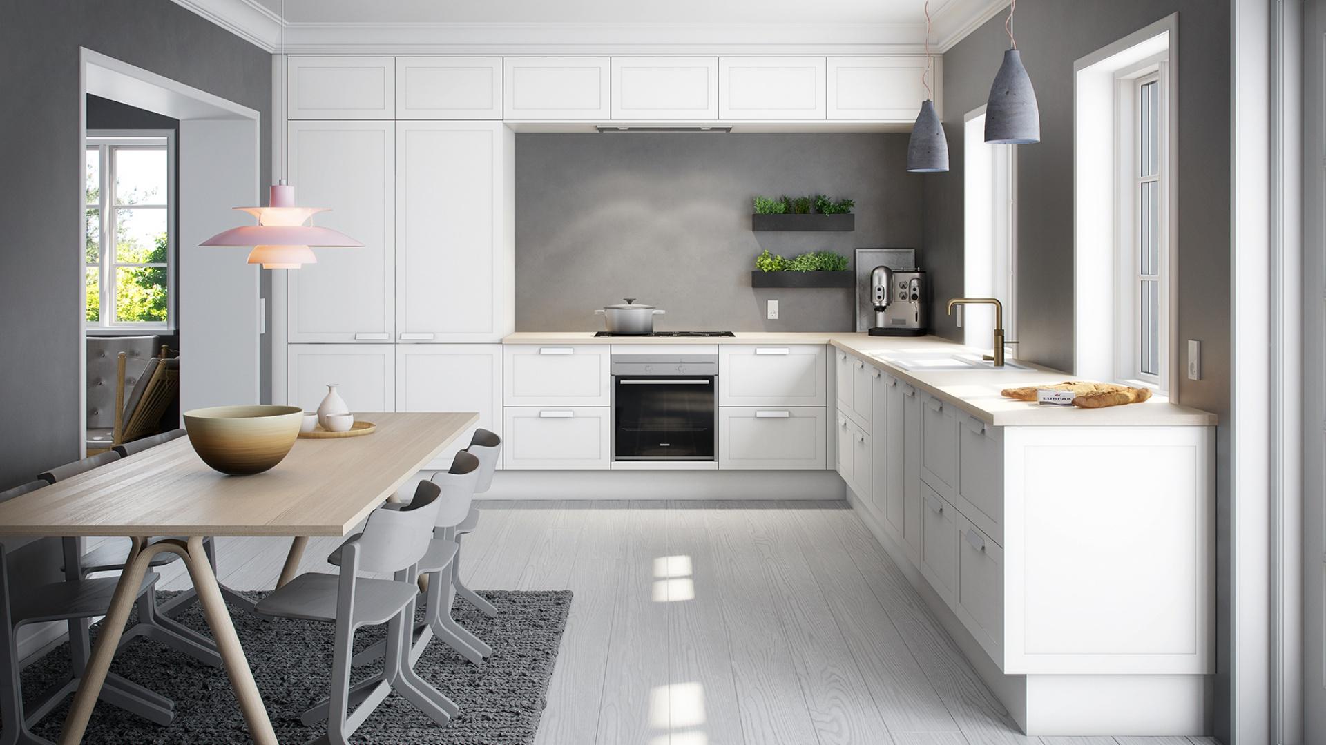 Bielone drewno na podłodze oraz blat kuchenny i stół jadalniany w kolorze jasnego drewna wpisują się w strategię ocieplania chłodnej aranżacji kuchni. Pięknie harmonizują z białymi meblami i szarą ścianą nad blatem. Fot. Svane, kuchnia Retro.
