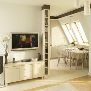 Niewielki salon urządzono z wykorzystaniem mebli i dodatków w kolorze ciepłego kremu. Do aranżacji ściany telewizyjnej wykorzystano klasyczną szafkę RTV. Projekt: Agnieszka Kubasik. Fot. Bartosz Jarosz.