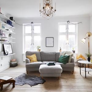 Salon może ubiegać się o miano ikony eklektyzmu. Stylizowana sofa i puf, industrialne, edisonowskie żarówki, zdobny żyrandol i vintage'owy metalowy stolik kawowy. Wszystkie te elementy zestawione ze sobą tworzą zaskakująco zgrane połączenie. Fot. Stadshem.se/Janne Olander.