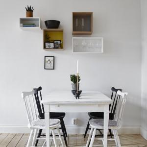 Mała jadalnia to niewielki stół pomalowany na biało i towarzyszące mu krzesła - dwa białe i dwa czarne. Fot. Stadshem.se/Janne Olander.