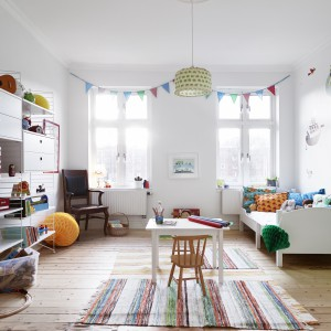 W pokoju dziecięcym znalazło się dużo miejsca do swobodnych zabaw, łóżko, praktyczny regał i niewielkie biurko. Jasne ściany zdobią wesołe, kolorowe rysunki. Fot. Stadshem.se/Janne Olander.