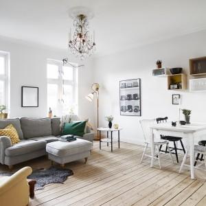W salonie wygospodarowano miejsce na niewielką jadalnię. Przestronności wnętrzu dodaje brak dużego dywanu (zastąpionego przytulnym, ale małym dywanikiem), białe ściany oraz wysokie okna. Fot. Stadshem.se/Janne Olander.