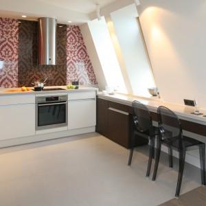 W kuchni na poddaszu ścianę ze skosem wykorzystano na przymocowanie niewielkiego blatu, pełniącego rolę stołu. Projekt: Małgorzata Borzyszkowska. Fot. Bartosz Jarosz.
