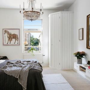 W tej sypialni wprowadzono dekoracyjne elementy. Bogato zdobiony żyrandol oraz ozdobna rama obrazu wprowadzają do wnętrza odrobinę eleganckiej klasyki. Fot. Alvhem Mäkler.