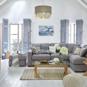 Miękką sofa narożna w jasnoniebieskim kolorze to centralny element wyposażenia salonu. Wraz z niewielkimi stolikami kawowymi o ciekawej formie tworzy swoiste centrum wypoczynku i relaksu. Fot. Dunelm.