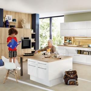 Biała kuchnia z elementami w kolorystyce drewna - ciepła, rodzinna, przytulna. Dzięki zróżnicowanym głębokościom szafek, przestrzeń można indywidualnie zagospodarować, np. zabudowując nieustawne wnęki. Ciekawym elementem kuchni jest też otwarta półka pod blatem dolnej zabudowy. Fot. Ballerina Kuechen, kolekcja XL 3146.