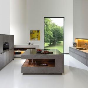 Fronty kuchni ze wzorem stylizowanym na zacierany beton - są wykończone ręcznie. Aranżację ocieplają wstawki w kolorystyce drewna. Ciekawy kształt ma wyspa kuchenna: w asymetrycznej, podświetlanej wnęce można eksponować ulubione drobiazgi czy ustawić książki. Fot. Rempp Kuechen, kolekcja Phoenix.