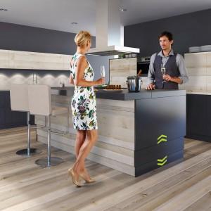System ergoAGENT nadaje się do kuchni z katalogów i na zamówienie. Po naciśnięciu specjalnego przycisku wyspa obniża się, dzięki czemu można przy niej wygodnie jeść posiłki, albo podwyższa, zamieniając w wysoki bar podczas spotkań towarzyskich. Fot. Kesseboehmer.
