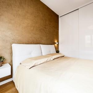 Jedną ze ścian sypialni całkowicie zabudowano wysoką zabudową, poprowadzoną pod sam sufit. Jej fronty wykończono w białym połysku, dzięki czemu powierzchnie odbijają światło i budują lekki klimat w pomieszczeniu. Projekt i zdjęcia: Brain Factory.