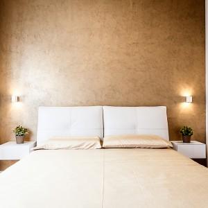 Ścianę za łóżkiem w sypialni wykończono pięknym, złotomiedzianym kolorem. Nadaje ona przestrzeni pokoju elegancki charakter. Na jej tle wyróżniają się białe, wiszące półki, na których zamiast lampek nocnych, postawiono doniczki z zielonymi kwiatami. Projekt i zdjęcia: Brain Factory.