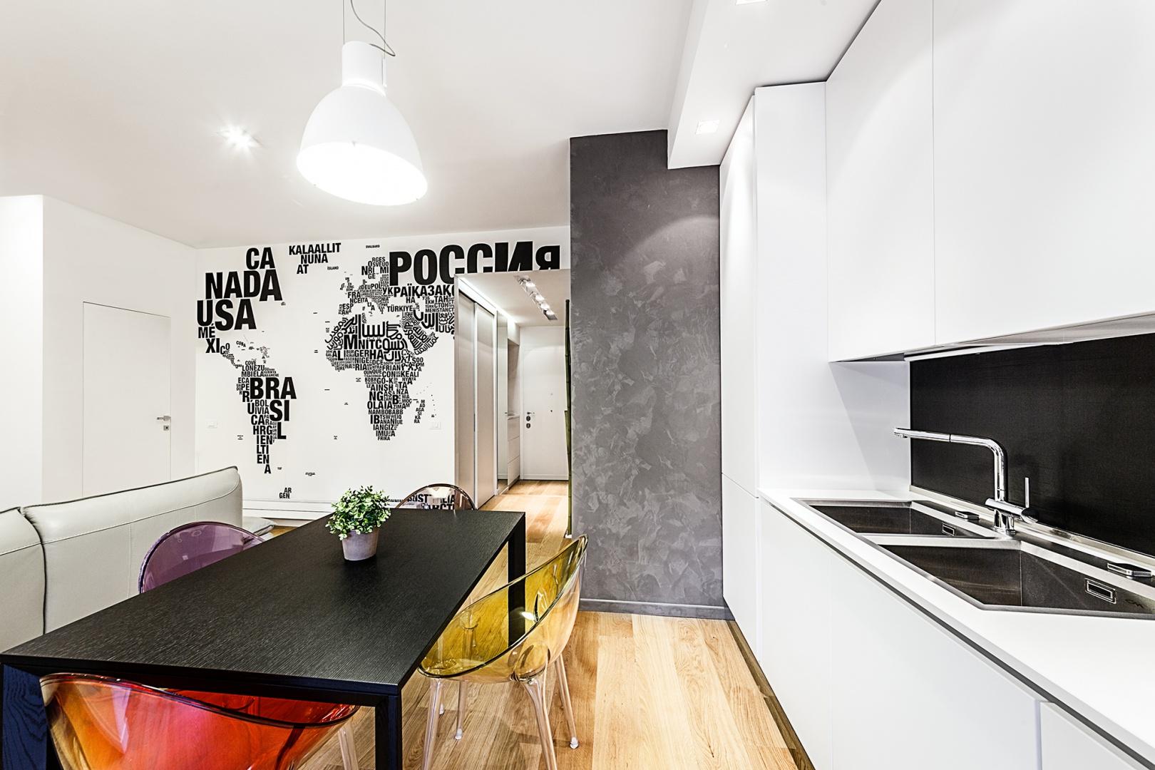 Ścianę nad blatem wykończono w czarnym kolorze, który efektownie kontrastuje z białymi meblami kuchennymi. Czarna powierzchnia koresponduje z kolei z ciemnym stołem jadalnianym i teksturą na ścianie w salonie. Projekt i zdjęcia: Brain Factory.
