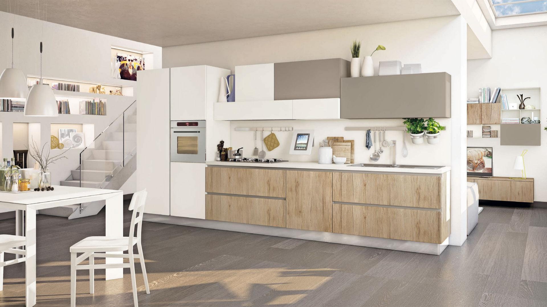 Kuchnia z kolekcji Immagina to piękne połączenie białych frontów w macie, szarych satynowych powierzchni, delikatnie zaakcentowanych jedynie w górnych rzędzie szafek oraz dolnej zabudowy w kolorze ciepłego drewna. Fot. Lube Cucine.