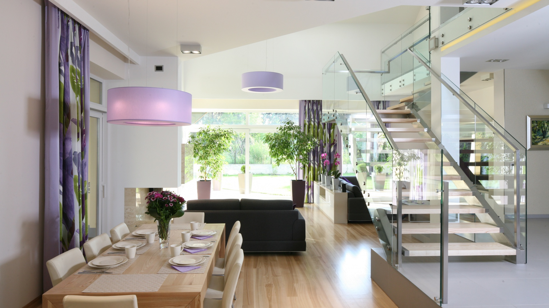 Lekka konstrukcja schodów, oparta na metalu i szkle nie zakłóca pastelowej aranżacji salonu połączonego z jadalnią. Stopnie wykonane zostały z tego samego rodzaju drewna co podłoga. Projekt: Monika i Adam Bronikowscy. Fot. Bartosz Jarosz.