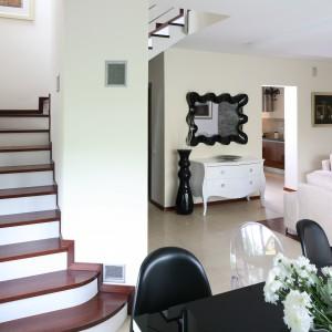 Elegancka konstrukcja schodów wpisuje się aranżację salonu. Tak jak ciemne dodatki przełamują białą aranżację pokoju dziennego, tak okładzina z drewna urozmaica wygląd schodów. Projekt: Piotr Stanisz. Fot. Bartosz Jarosz.
