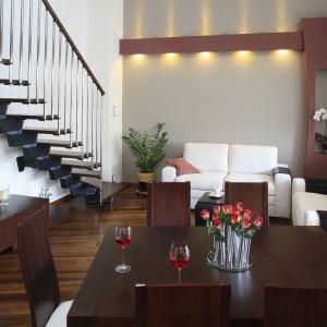 Ażurowa konstrukcja schodów rozpościerających się na ścianie w salonie, efektownie dekoruje przestrzeń telewizyjną. Projekt: Jolanta Kwilman. Fot. Bartosz Jarosz.