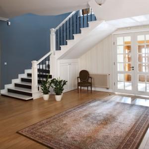Eleganckie schody z drewnianymi tralkami podkreślają elegancki wygląd przestronnego salonu w stylu klasycznym. Projekt: Maciej Bołtruczyk. Fot. Monika Filipiuk-Obałek.