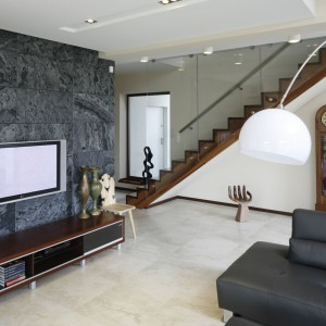 Długie, drewniane schody zabezpieczono szklaną balustradą. W ten sposób konstrukcja łączy w element tradycyjny i nowoczesny, wpisując się w projekt salonu. Projekt: Piotr Stanisz. Fot. Bartosz Jarosz.