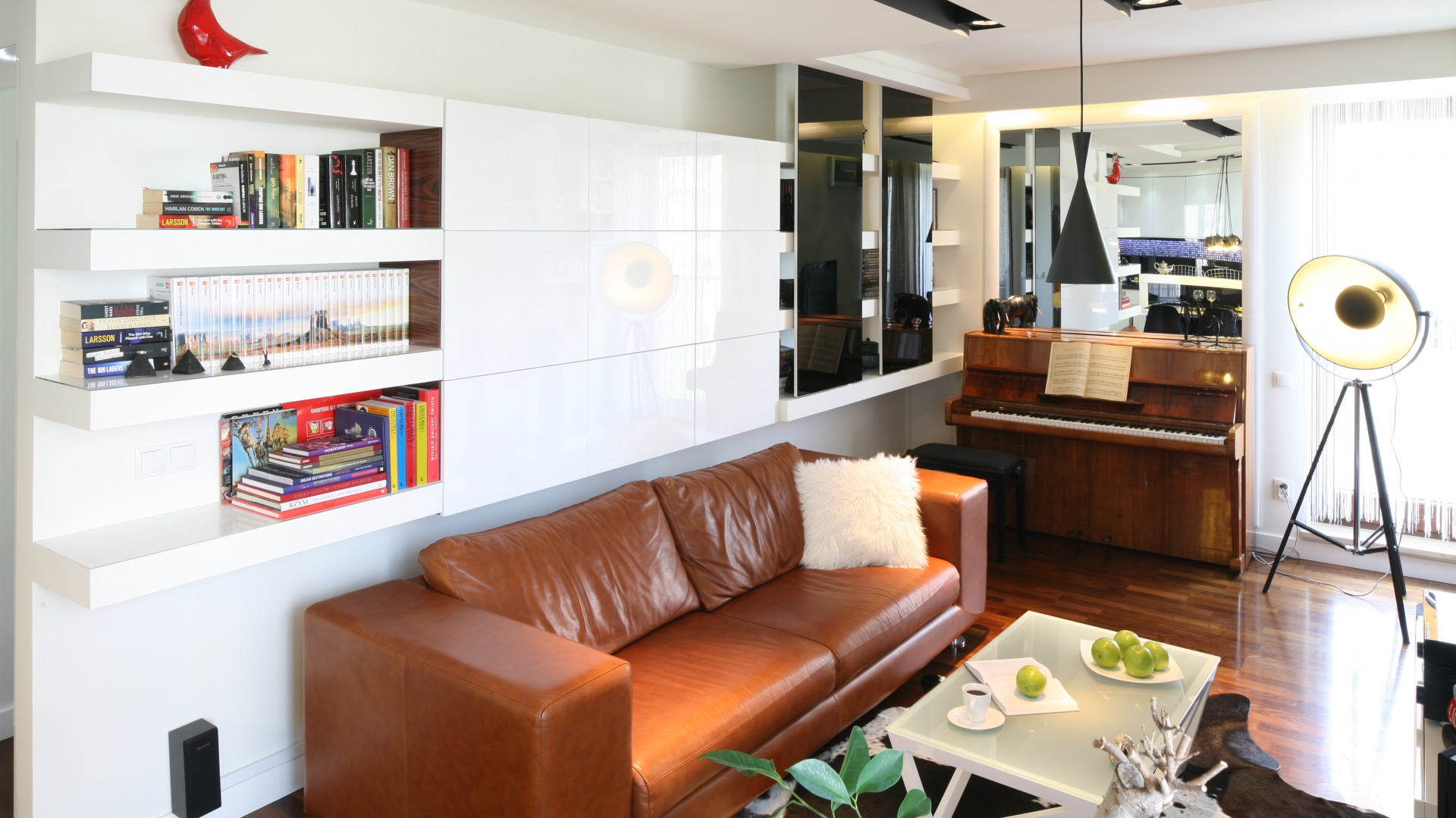 Niedużą przestrzeń wąskiego, lecz długiego salonu urządzono tak, by efektywnie wykorzystać każdy metr. Stąd nad sofą pojawiają się praktyczne półki i szafeczki, a ścianę za pianinem zdobi lustro, które optycznie podwaja przestrzeń. Projekt: Małgorzata Mazur. Fot. Bartosz Jarosz.