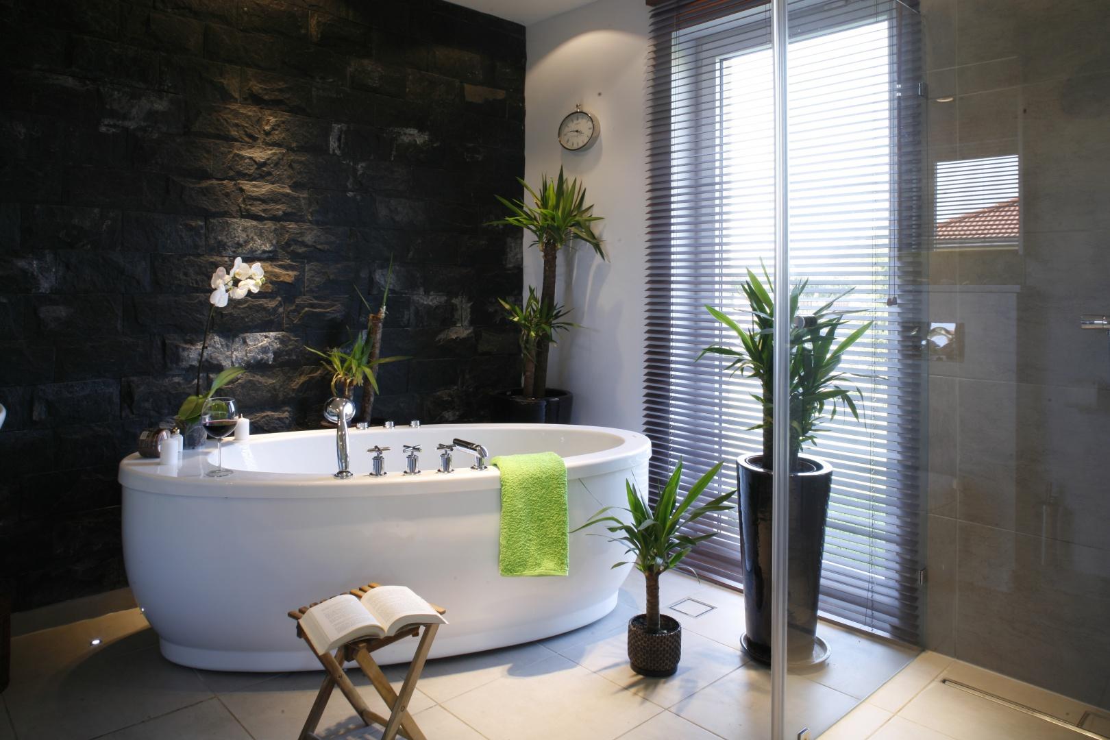 Podobnie jak w sypialni, również w łazience ścianę zdobi kamień - łupek naturalny. W tak dużym pomieszczeniu zainstalowano zarówno wannę wolno stojącą, jak i prysznic. Projekt: Katarzyna Merta-Korzniakow. Fot. Monika Filipiuk-Obałek.