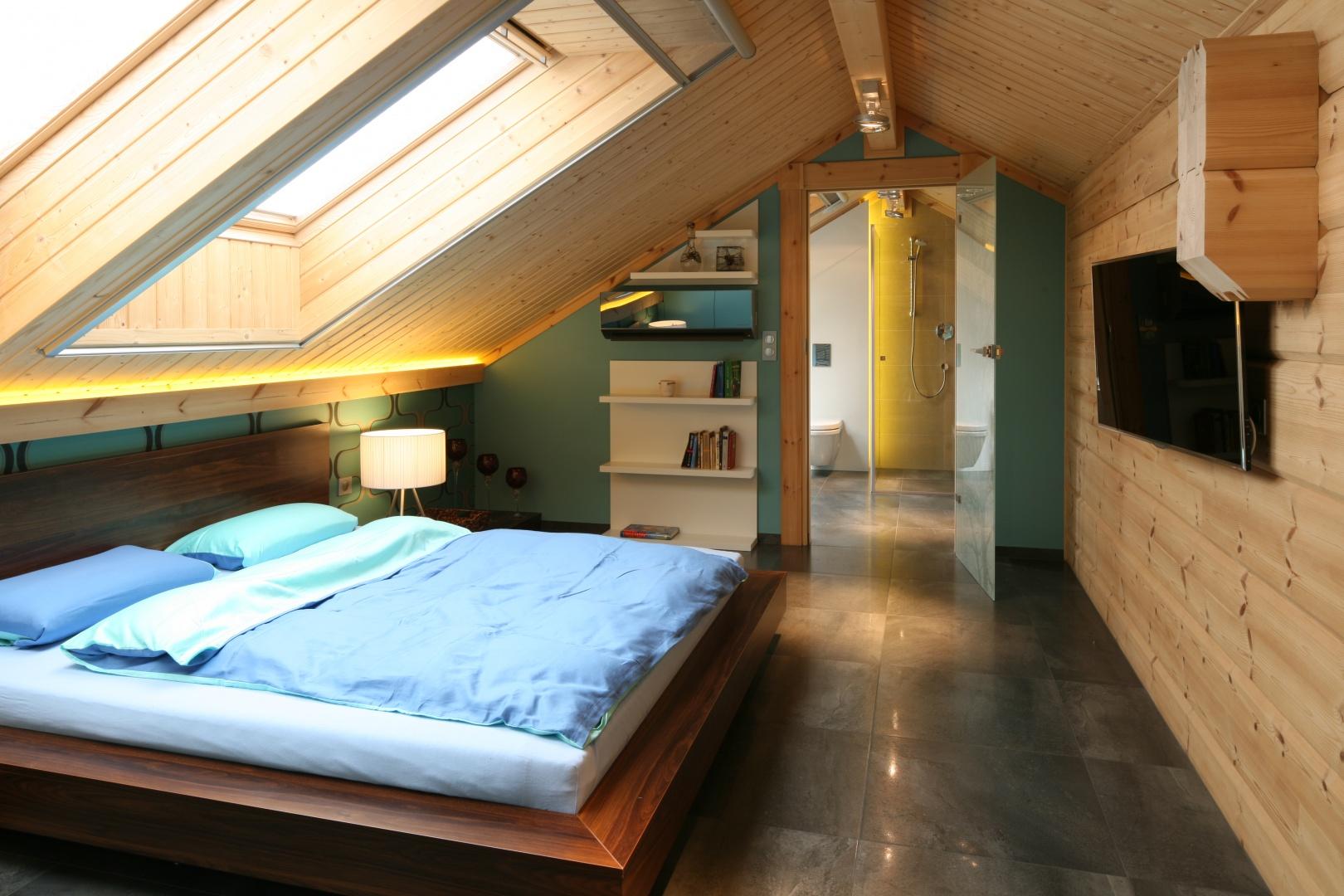 Sypialnia na poddaszu, tak jak cały dom, wykończona jest drewnem, które nadaje temu wnętrzu ciepły klimat. Szare płytki natomiast, rozciągające się także w łazience, kreują nowoczesny styl wnętrza. Projekt: Tomasz Motylewski, Marek Bernatowicz. Fot. Bartosz Jarosz.