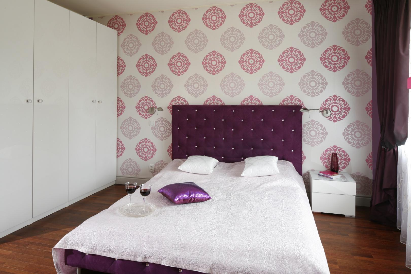 Tapicerowane łóżko oraz dekoracyjna tapeta wskazują, że jest to sypialnia eleganckiej gospodyni. W związku z tym nie mogło przy niej zabraknąć eleganckiej łazienki. Projekt: Beata Ignasiak-Wasik. Fot. Bartosz Jarosz.