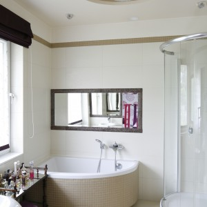 Łazienkę wyposażono w wannę narożną, w której można wziąć relaksującą kąpiel przez dnem. O poranku natomiast sprawdzi się prysznic, ukryty za półokrągłą kabiną. Projekt: Beata Ignasiak-Wasik. Fot. Bartosz Jarosz.