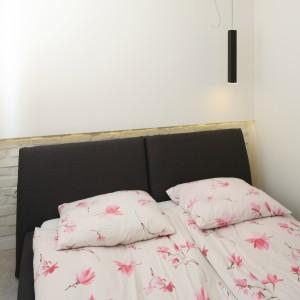W niewielkiej sypialni dominuje biel i jasne drewno, dzięki czemu wnętrze wydaje się większe. Jedynym ciemnym elementem jest brązowe łóżko. Projekt: Dominik Respondek. Fot. Bartosz Jarosz.