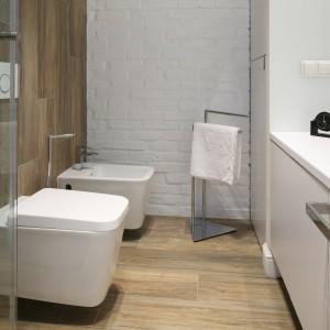Wnętrze łazienki wyłożono drewnem oraz białymi płytkami z kamienia. Szafki z frontami lakierowanymi na wysoki połysk korespondują z gładką fakturą sanitariatów. Projekt: Dominik Respondek. Fot. Bartosz Jarosz.