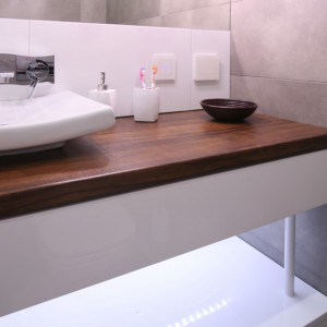 Łazienkę utrzymaną w białej i szarej tonacji ocieplono drewnianym blatem. Projekt: Karolina Łuczyńska. Fot. Bartosz Jarosz.