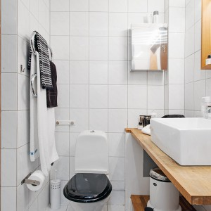 Drewniany blat, rama lustra i półka umieszczona pod umywalką ocieplają jasne wnętrze łazienki. Fot. Alvhem Mäkler.