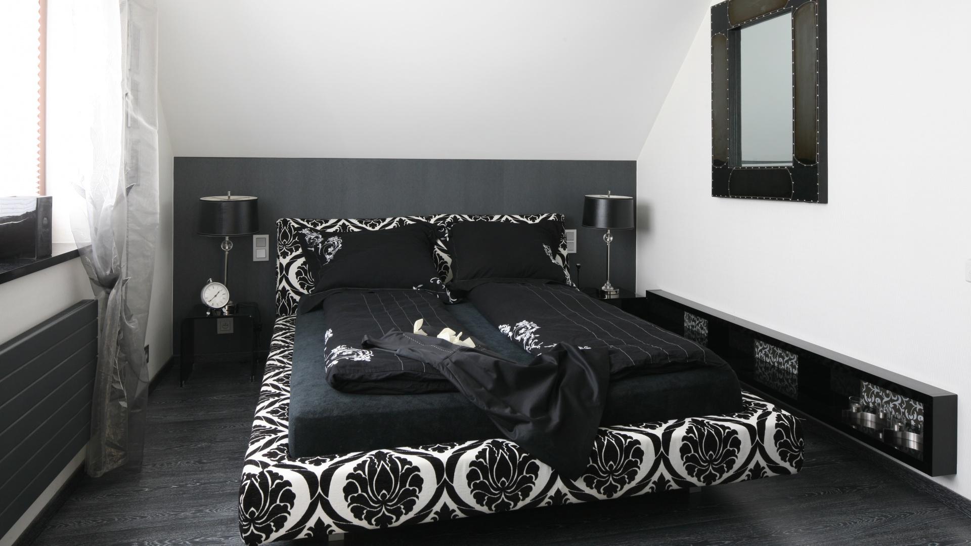 Modny duet czerni i bieli nadaje charakteru nowoczesnej sypialni. Chociaż wnętrze nie należy do dużych, uwzględniono w nim także łazienkę, schowaną za otwartą ścianą. Wchodzi się do niej bezpośrednio z sypialni. Projekt: Małgorzata Borzyszkowska. Fot. Bartosz Jarosz.