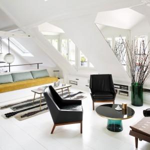 Jasny salon pod skosami rozświetla naturalne światło wpadające do środka przez duże okna i odbijające się od dominującej we wnętrzu bieli. Projekt: Sarah Lavoine. Fot. Francis Amiand.