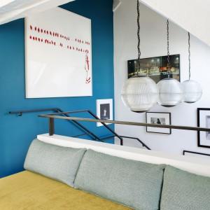 Schody prowadzą do salonu, a każdemu krokowi towarzyszą fotografie zdobiące całą wysoką ścianę, zamykającą klatkę schodową. Prostopadła ściana została pomalowana pięknym, niebieskim kolorem. Projekt: Sarah Lavoine. Fot. Francis Amiand.