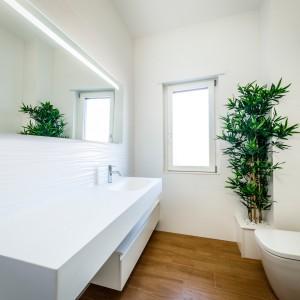 Ceramika i meble w łazience mają geometryczne, kubistyczne kształty, a lustro nad umywalką pozbawione jest ram, dzięki czemu wpisuje się w nowoczesny charakter przestrzeni. Projekt i zdjęcia: Marco Marotto, Paola Oliva, Brain Factory.
