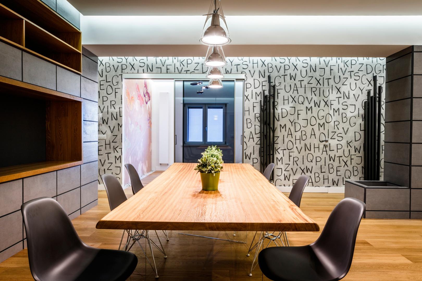 Ściana z oryginalnymi napisanymi, wyglądającymi jakby zostały nakreślone węglem wprowadza do wnętrza surowy charakter i efektownie kontrastuje z drewnianą podłogą i stołem. Projekt i zdjęcia: Marco Marotto, Paola Oliva, Brain Factory.